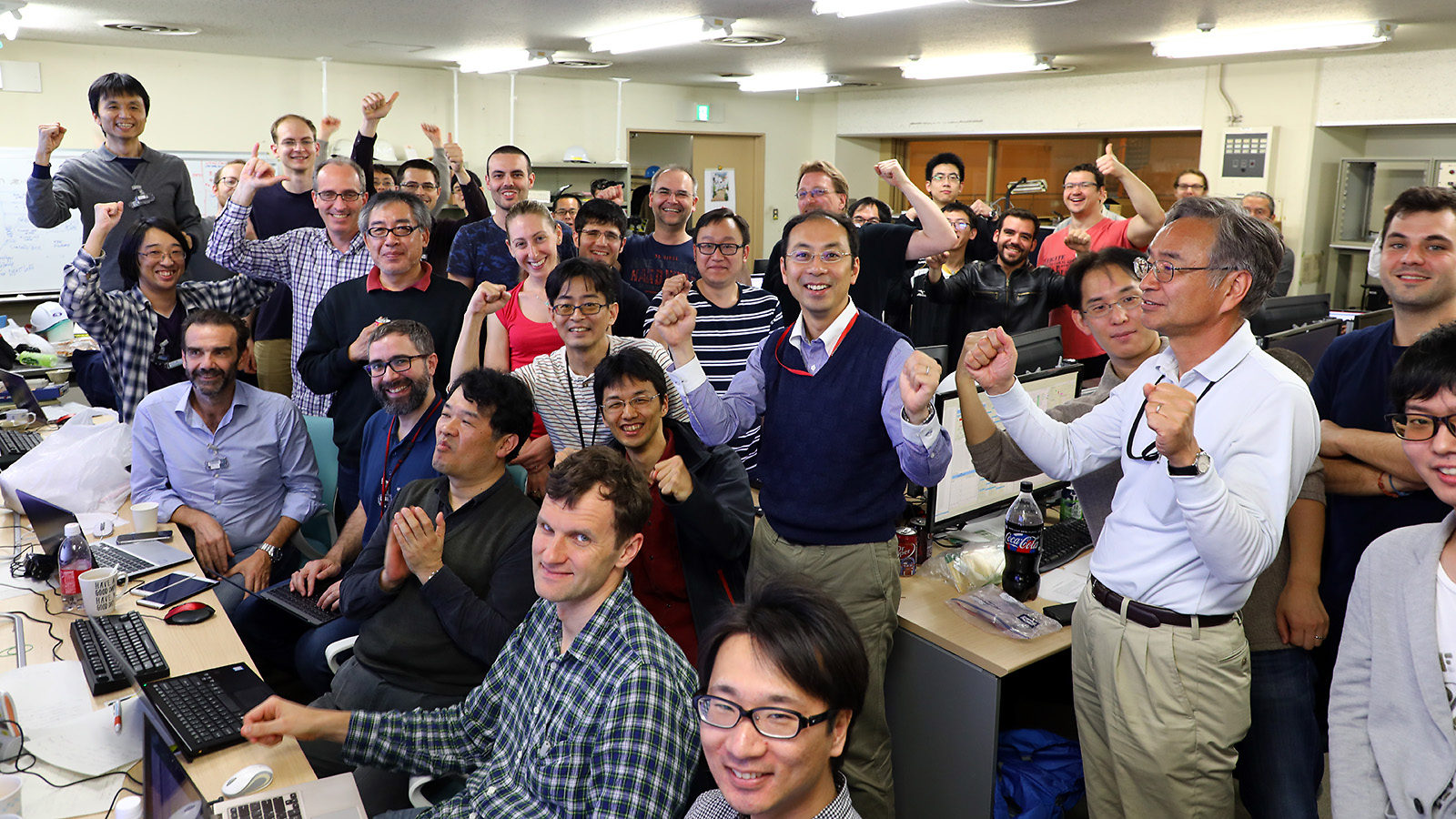 Photo of dozens of researchers celebrating in the control room after first collisions