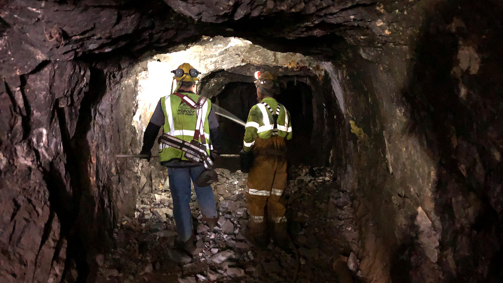 Two construction workers in a tunnel below ground