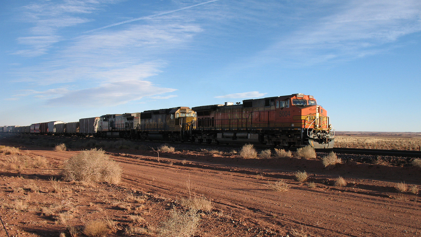 Photo of a train traveling along tracks out in the desert