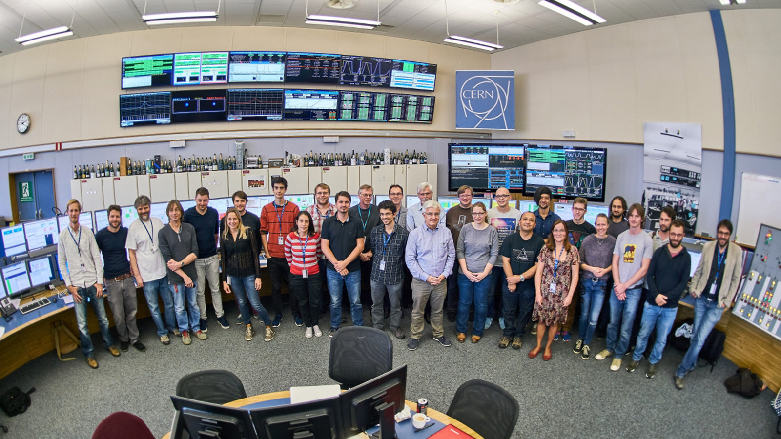 Group photo of about 30 people in the CERN Control Centre