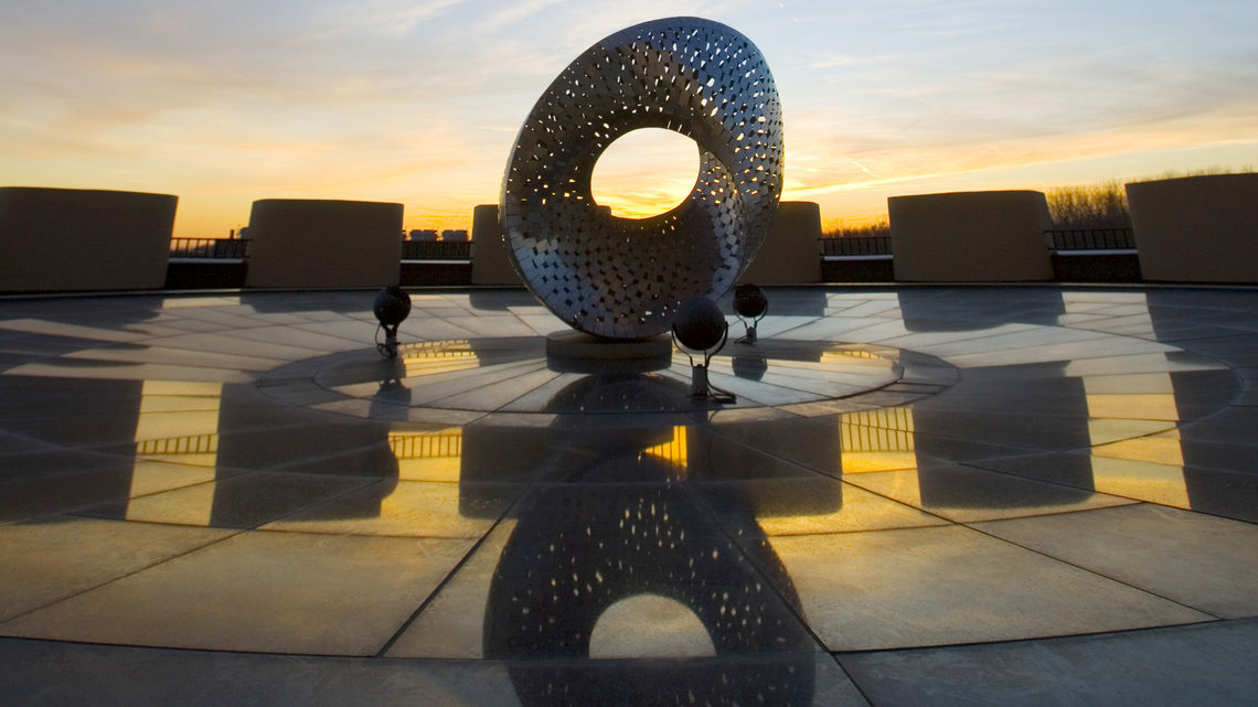 Photo of Fermilab founding director Robert Wilson's Mobius Strip sculpture atop Ramsey Auditorium