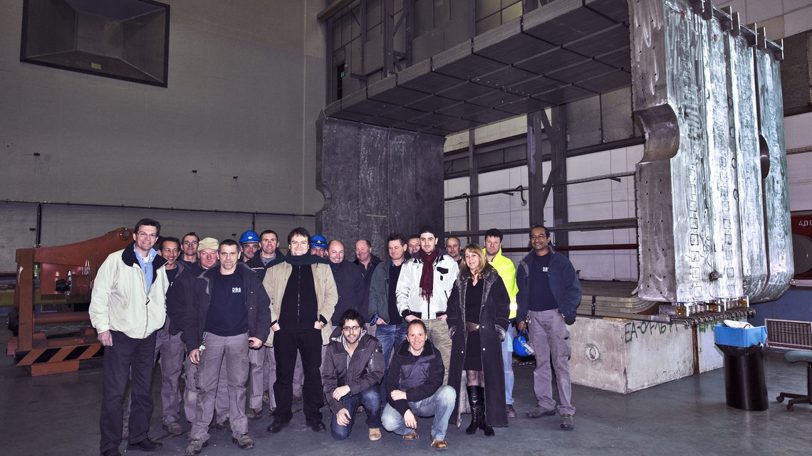 Team members in front of the magnet coils