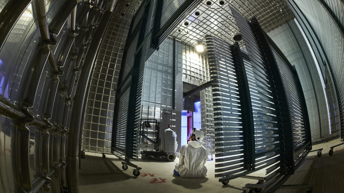 A person in cleanroom garb sits inside the ProtoDUNE detector.