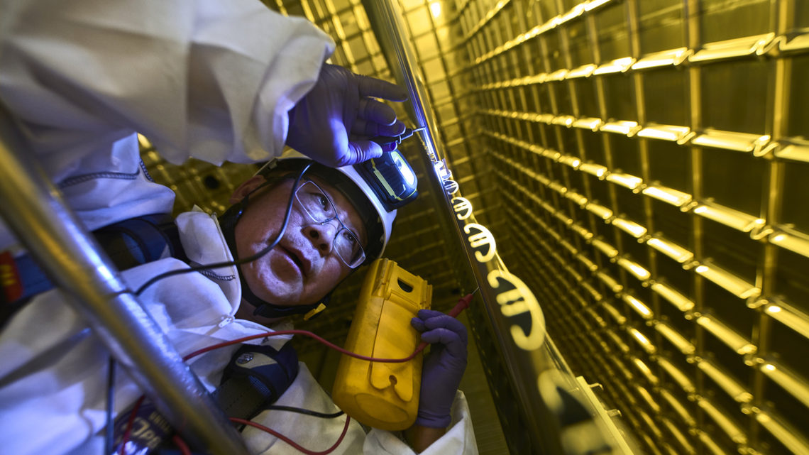 A person in a clean suit examines components of ProtoDUNE
