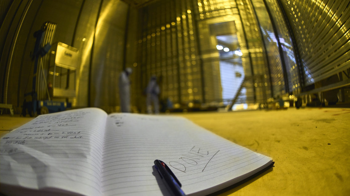 A researchers notebook in the foreground of the detector