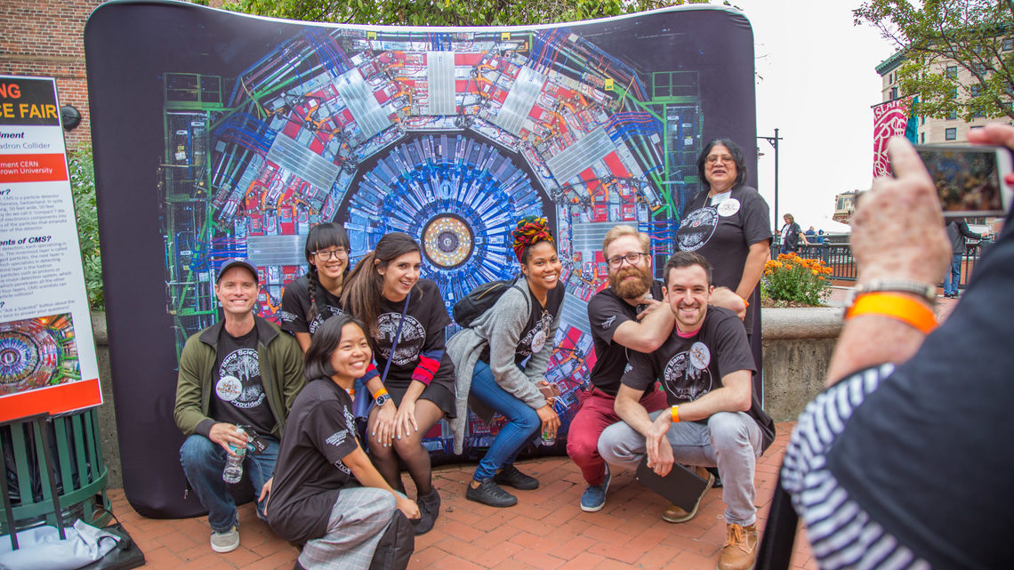 Group of scientists, professors, and volunteers posing in front a Big Bang Science Fair backdrop