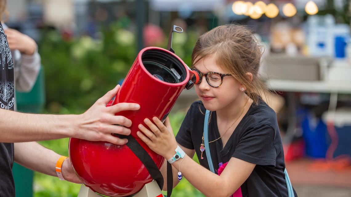 A girl peers through a solar telescope