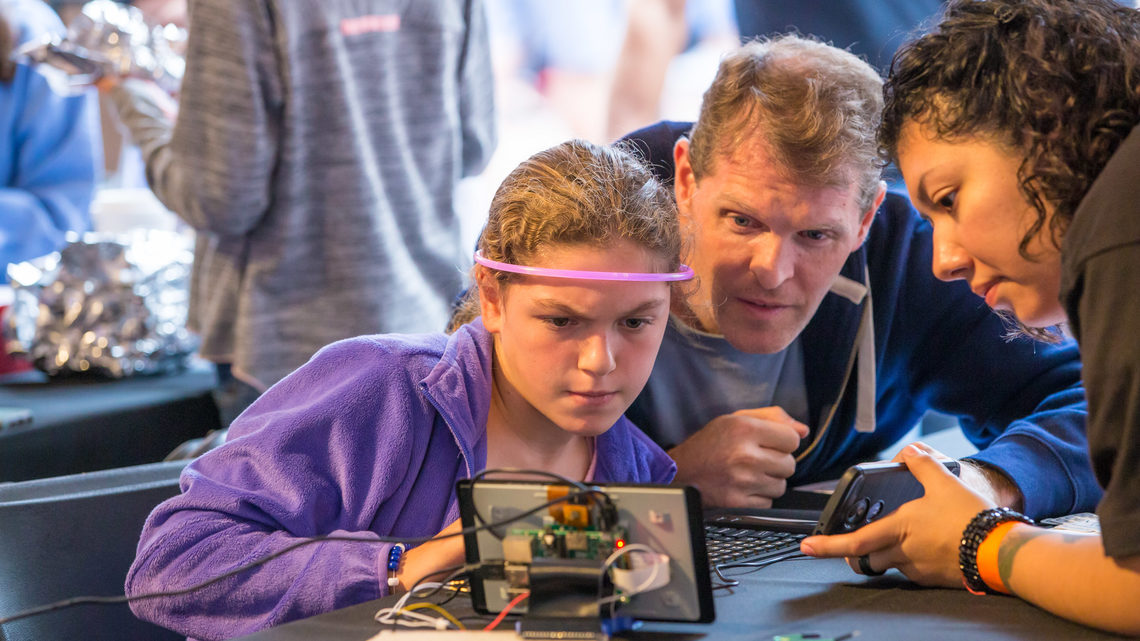 A young girl wearing a glowing headband participates in a hands-on science activity