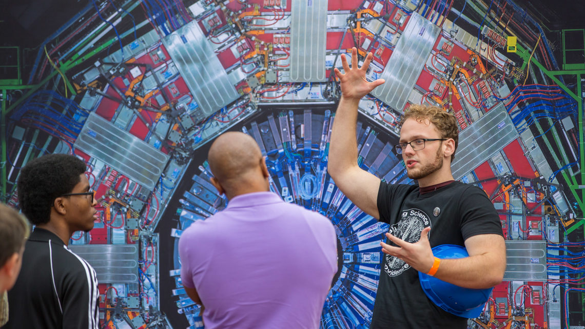 A volunteer explains the CMS experiment in front of an image of the CMS detector