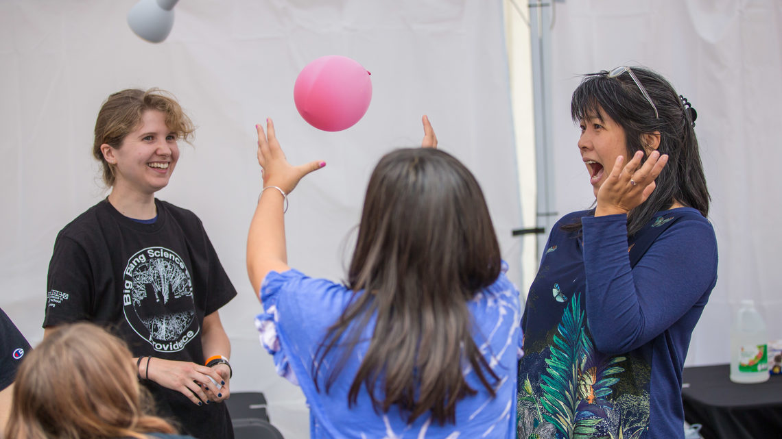 Attendees taking part in an experiment involving a balloon