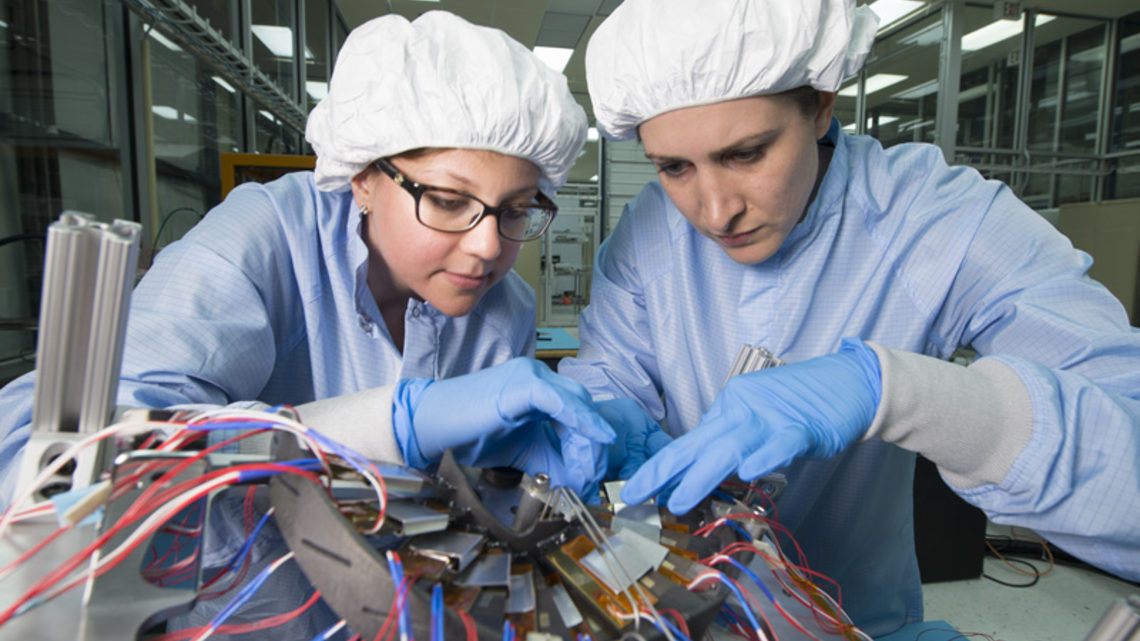 Scientists Maral Alyari and Stephanie Timpone, wearing clean room gear, inspect the detector.
