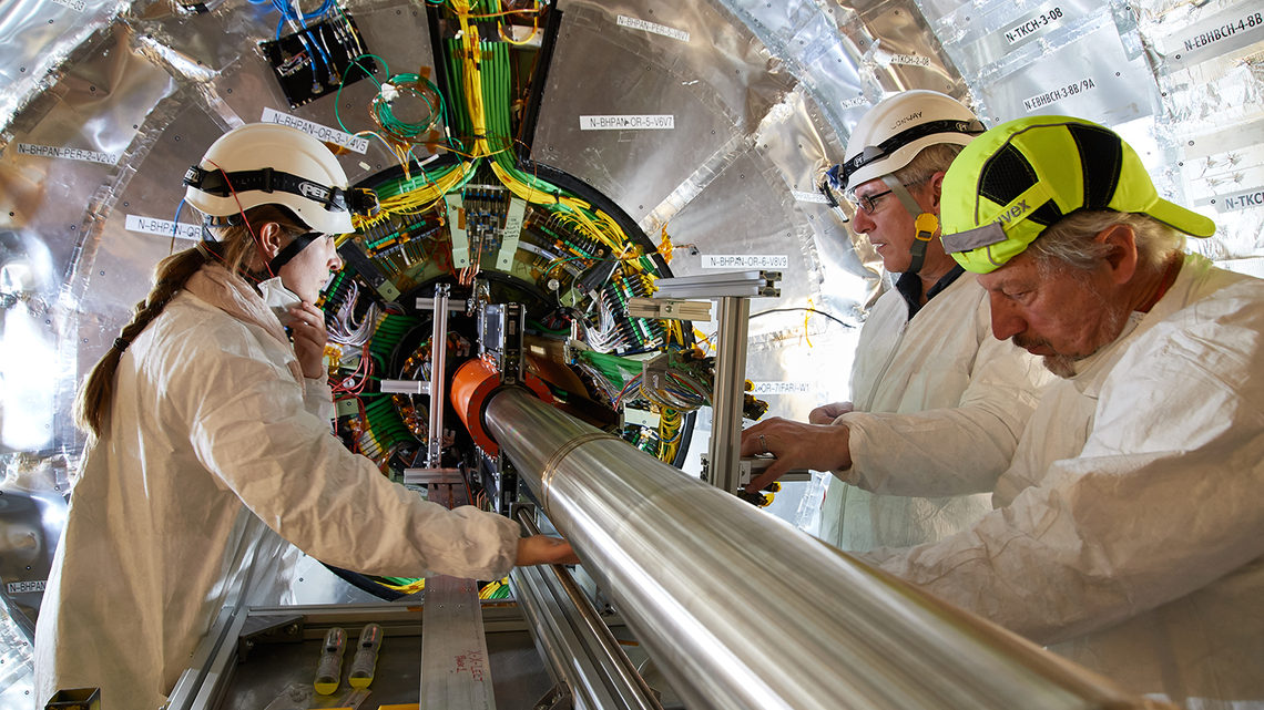Three scientists in protective helmets talk with their cleanroom masks pulled down or off.