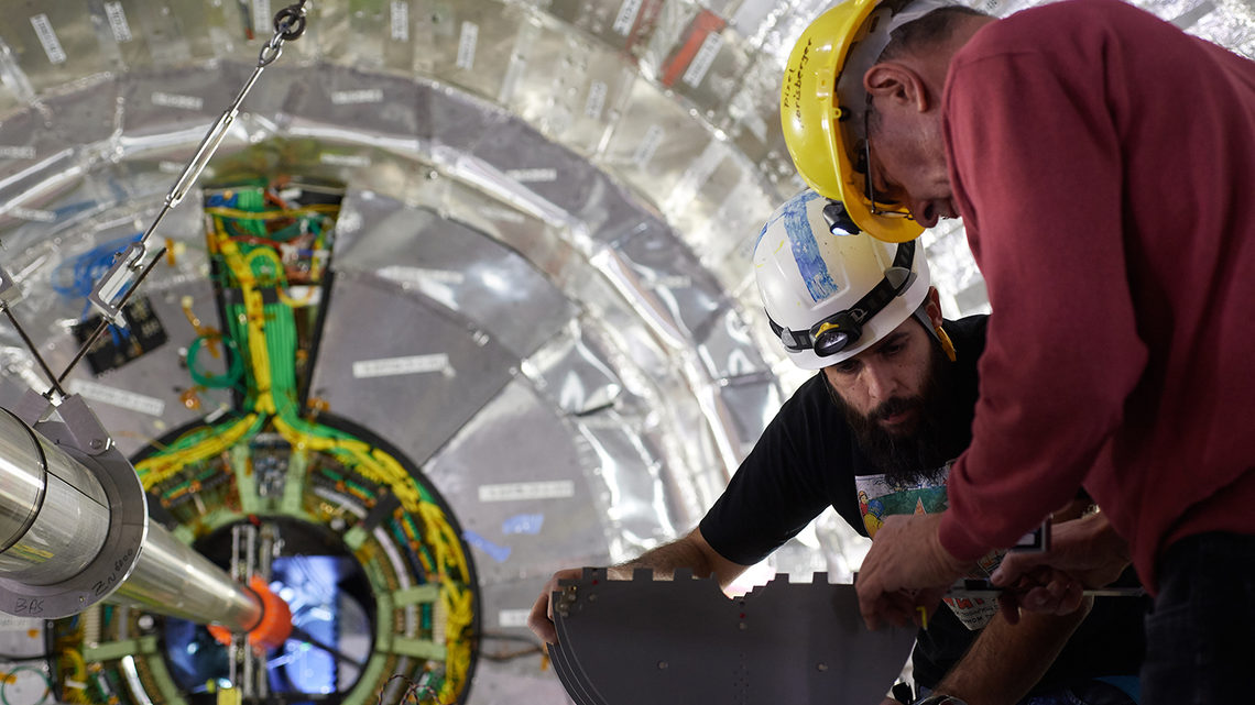 Two scientists in hard hats work with a mock-up next to the CMS detector.