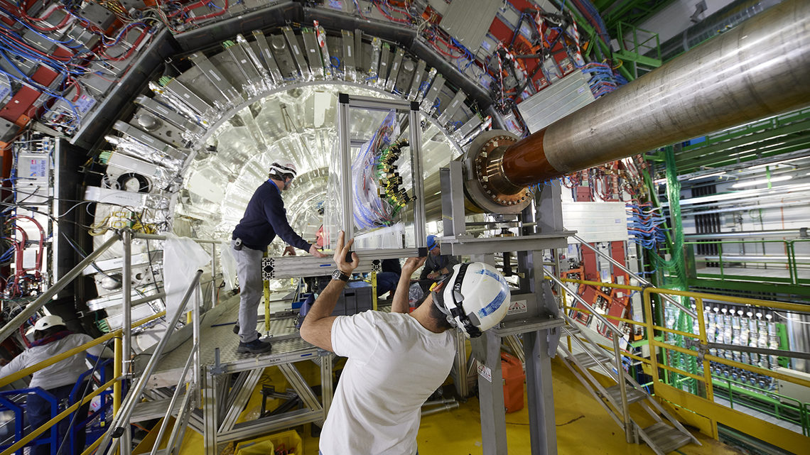People in hard hats insert new parts into the CMS detector.