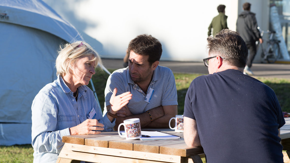 A woman and two men sitting at a picnic table talking