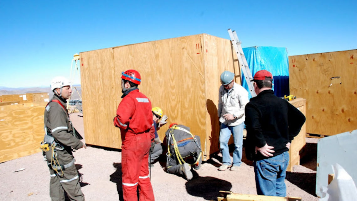 Photo of men on Dark Energy Camera site working on wooden crates in helmets and protective suits