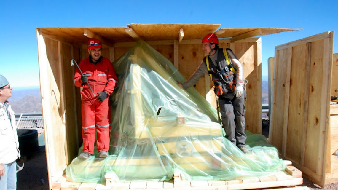 Photo of a support structure for the Dark Energy Camera sits shrouded in plastic while workers disassemble its crate