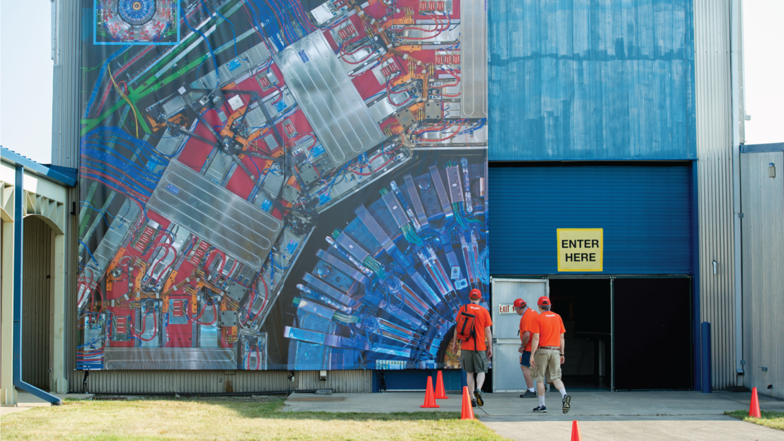 A section of the CMS detector at CERN is displayed on the side of a Fermilab building to provide visitors with a sense of scale.