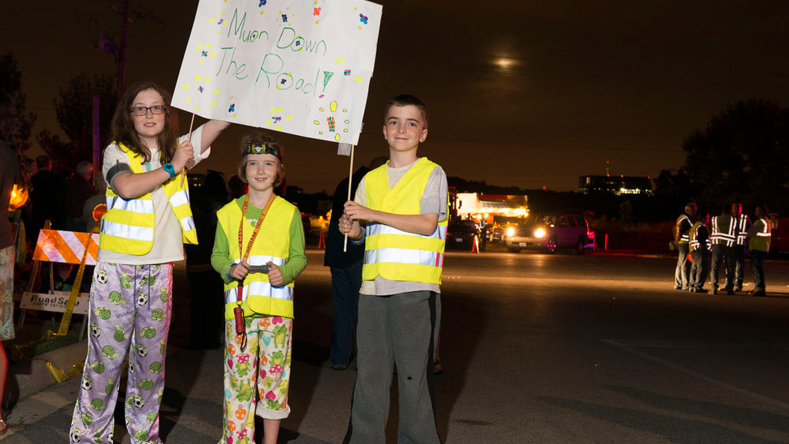 In their pajamas and safety vests, Maeve, Mary Kate and Kevin Pinkelman of Glen Ellyn, Illinois, cheered on the Muon g-2 ring