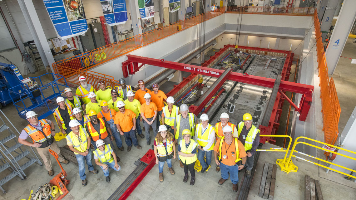 Members of the team responsible for moving the ICARUS modules stand in front of the detector.