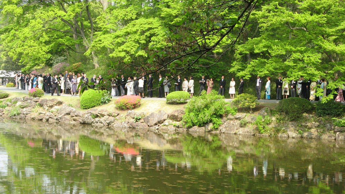 Attendees of the event stand along the water's edge