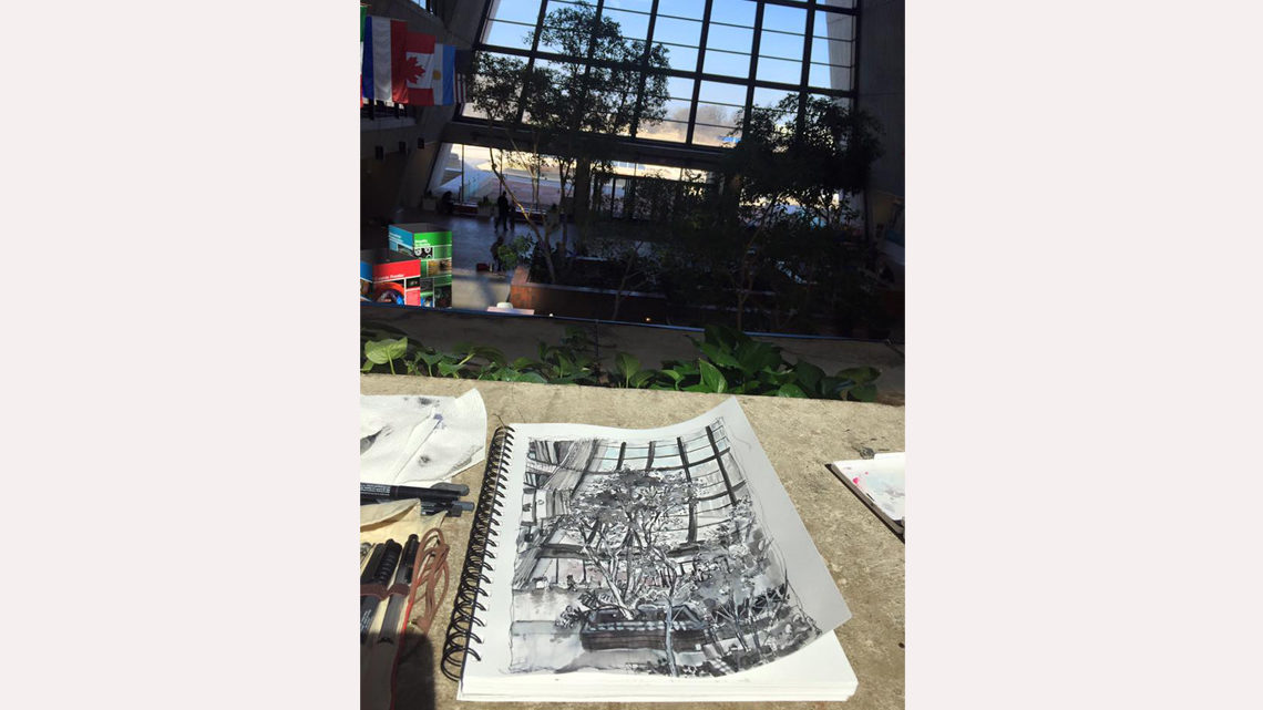 ink drawing of trees in Wilson Hall atrium in a notebook sitting on a ledge in Wilson Hall atrium