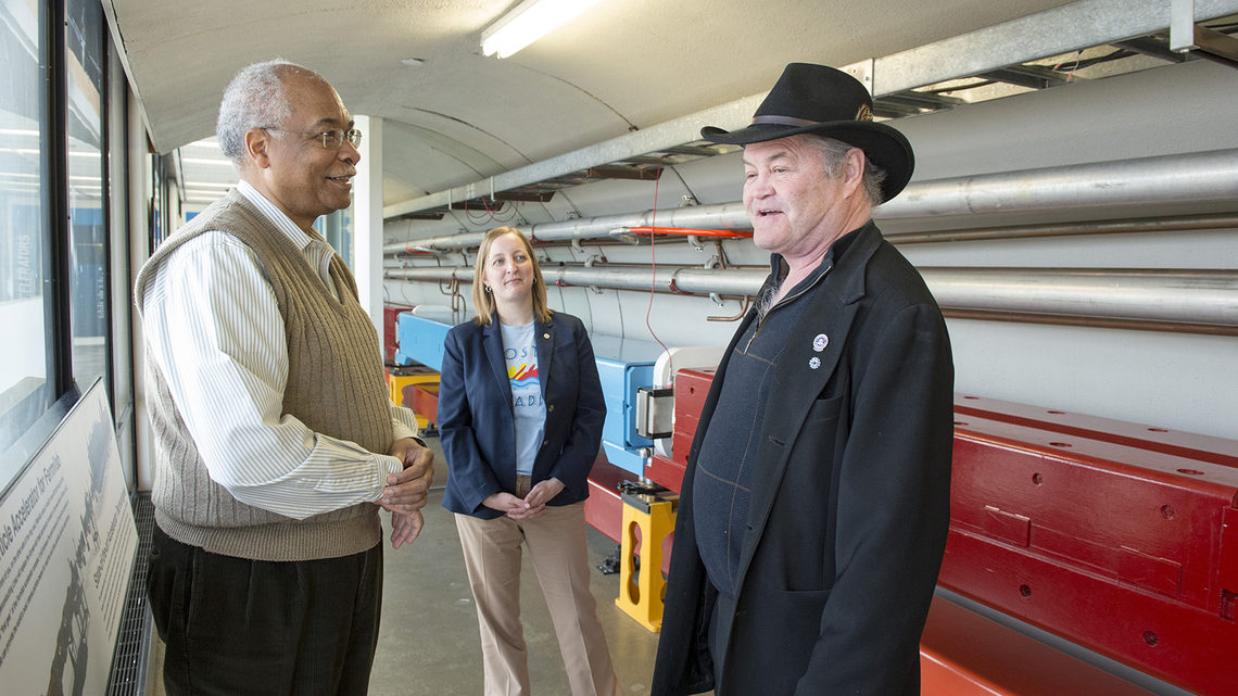 Monkee Micky Dolenz stands by a model particle accelerator with two Fermilab employees