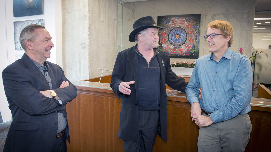 Former Monkee Micky Dolenz talks with the director and deputy director of Fermilab