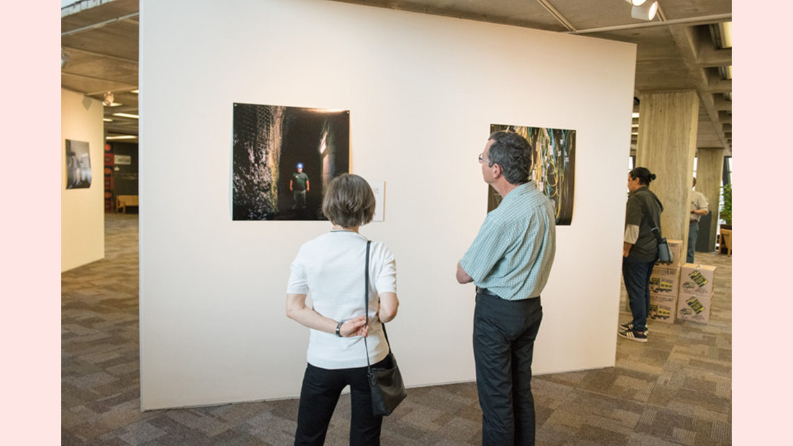 Photos in the exhibit are viewed by attendees