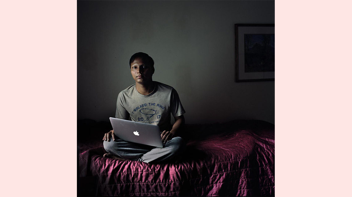 Photo of a young man with a laptop on a bed