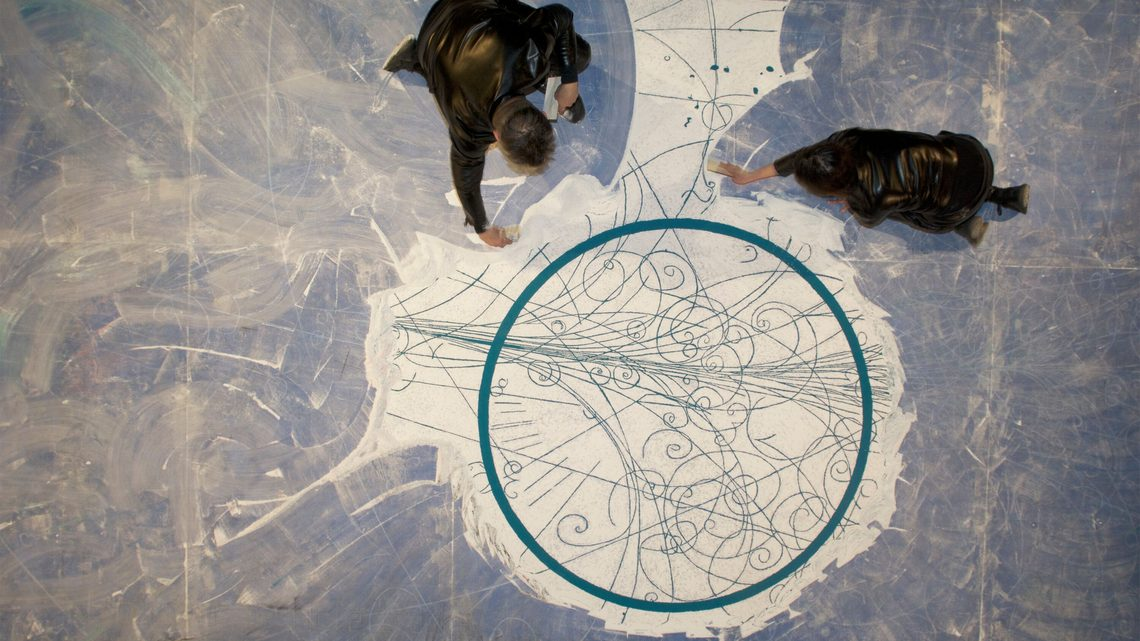 Overhead photograph of artists sweeping around the central circle