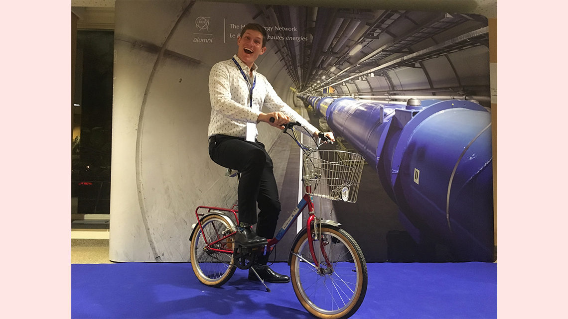 Pasner posing on a bike in front of an image of a CERN tunnel