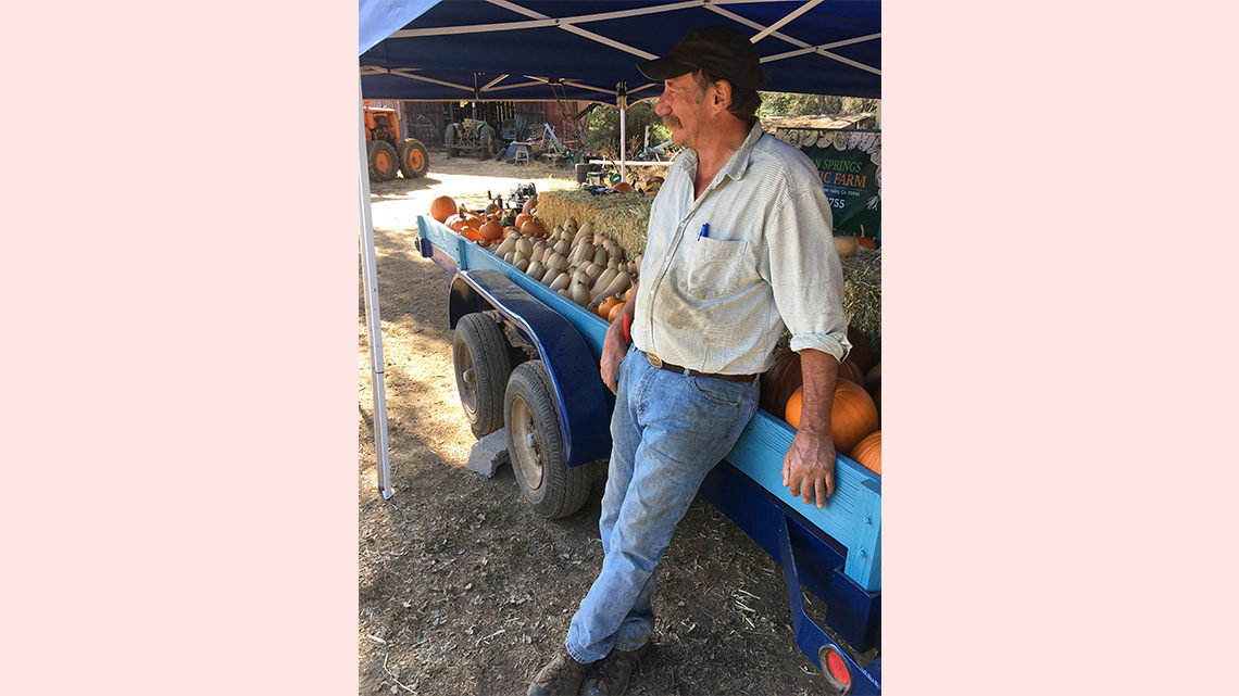 Pasner's dad rests next to a trailer full of produce