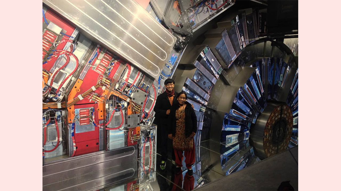 Photo of two people posing in front of a display that resembles the CMS detector