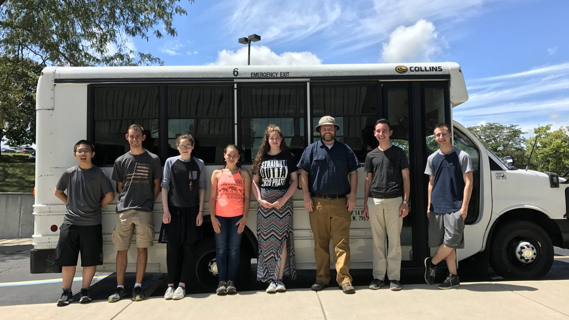Glenbrook North High School students standing beside bus