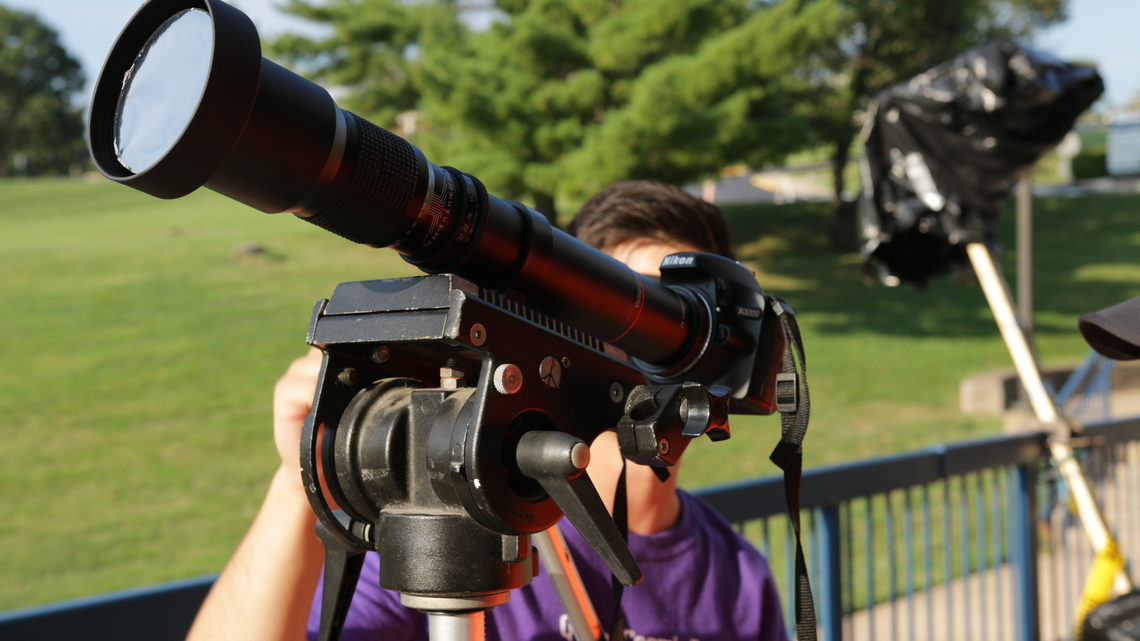 Student looking through telescope