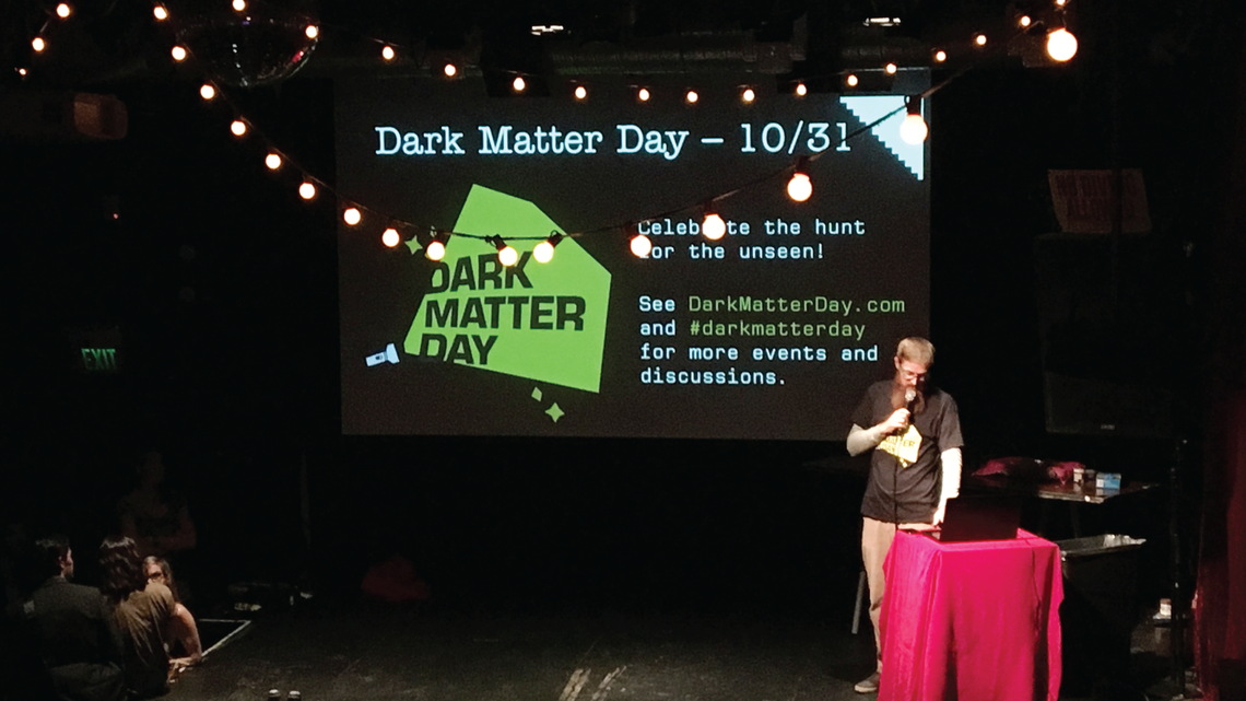 Bart Bernhardt, co-founder of Nerd Nite SF, donned a Dark Matter Day t-shirt during an October 18 event in San Francisco.