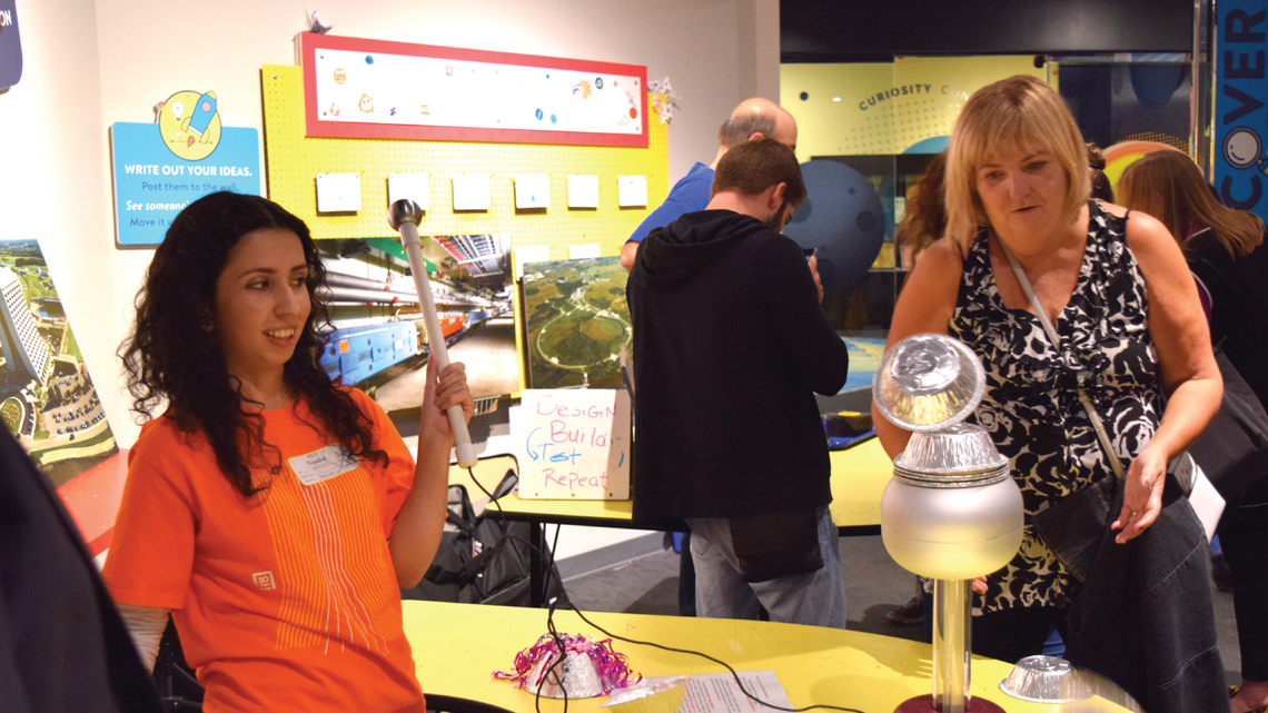 Photo of a volunteer demonstrating magnetism at a Dark Matter Day event at Adler Planetarium in Chicago