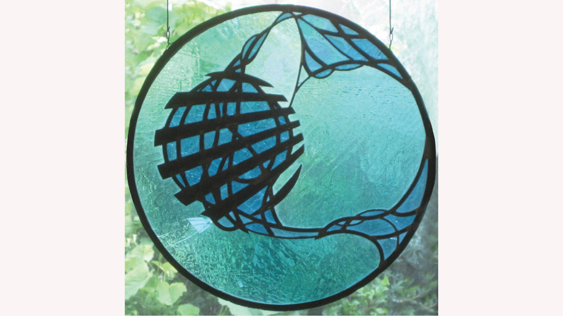 Circular stained glass piece in light and dark blue