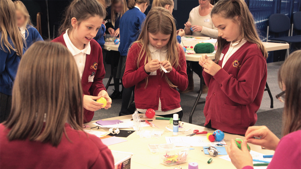 Photo of children making their own dark matter particles during a workshop at STFC's Rutherford Appleton Laboratory in the UK