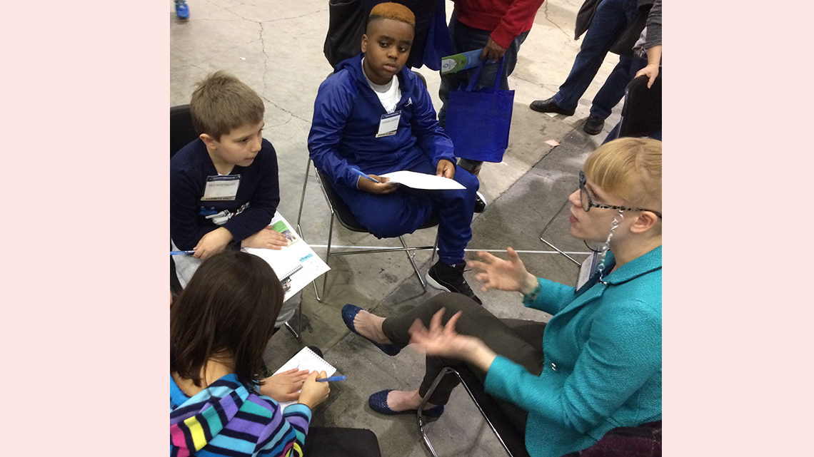 Children sitting around a scientist interviewing