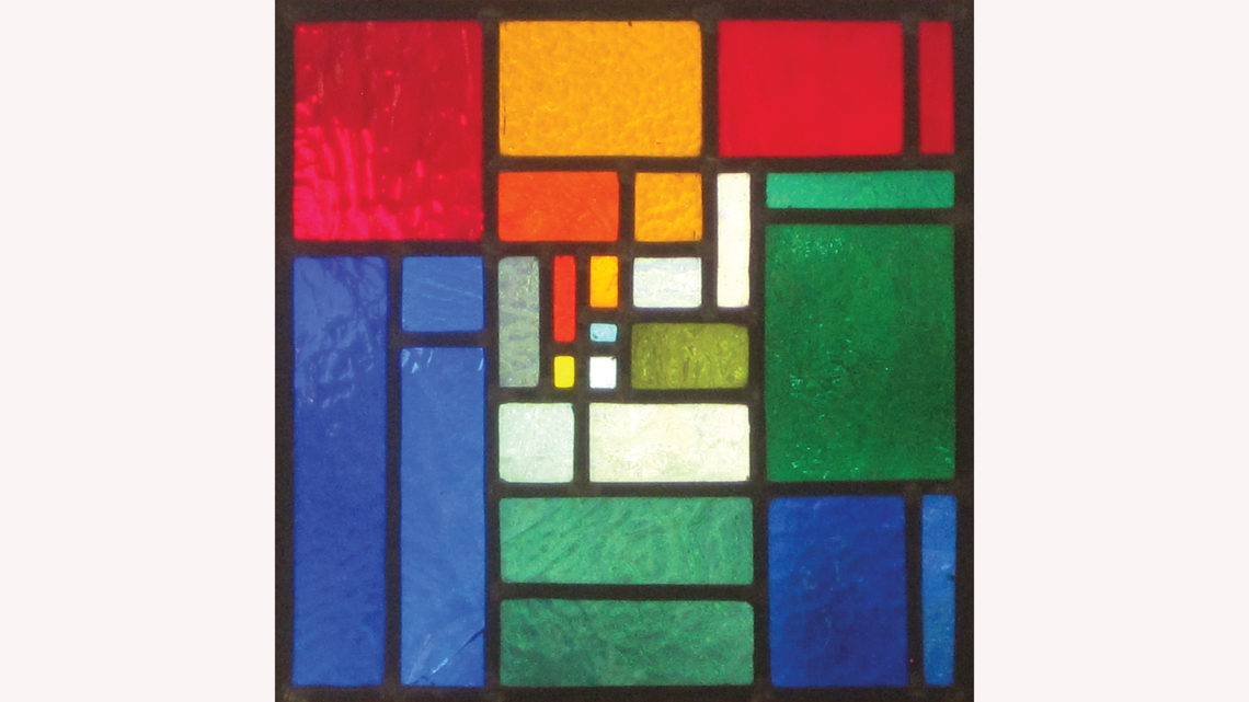 Square stained glass piece in red, yellow, green, and blue