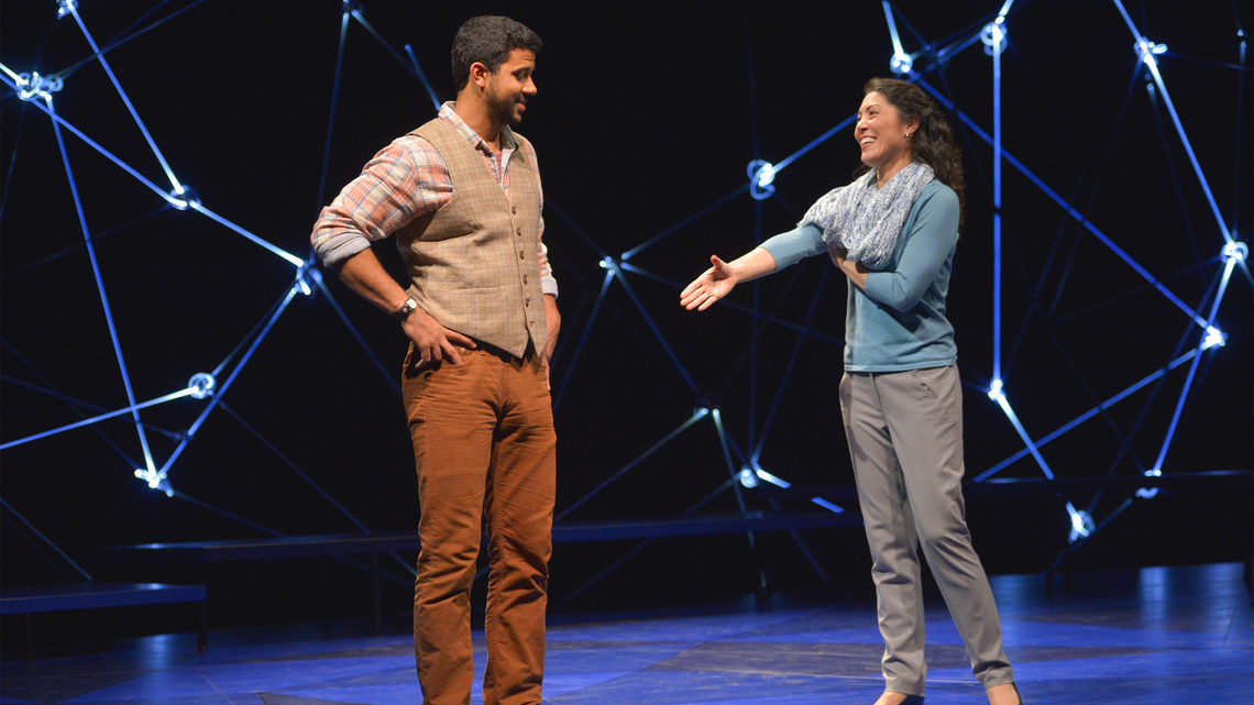 A scene from Constellations: a man and woman on stage she is reaching her hand out to him for a handshake