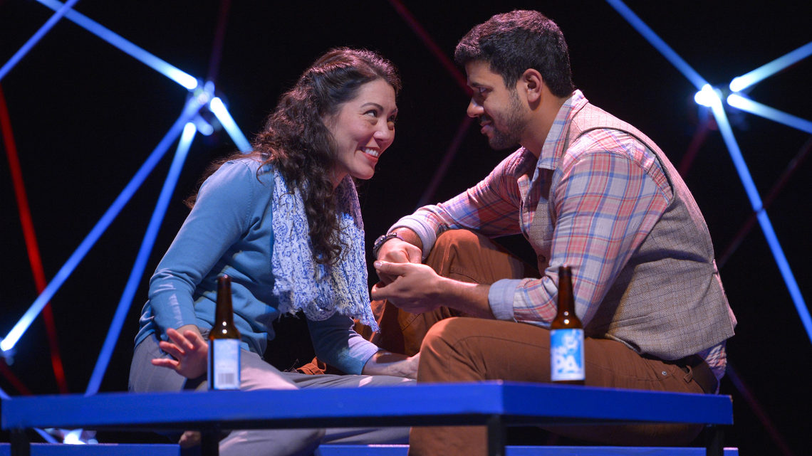 A scene from Constellations: a man and woman on stage both are sitting on a bench with beer