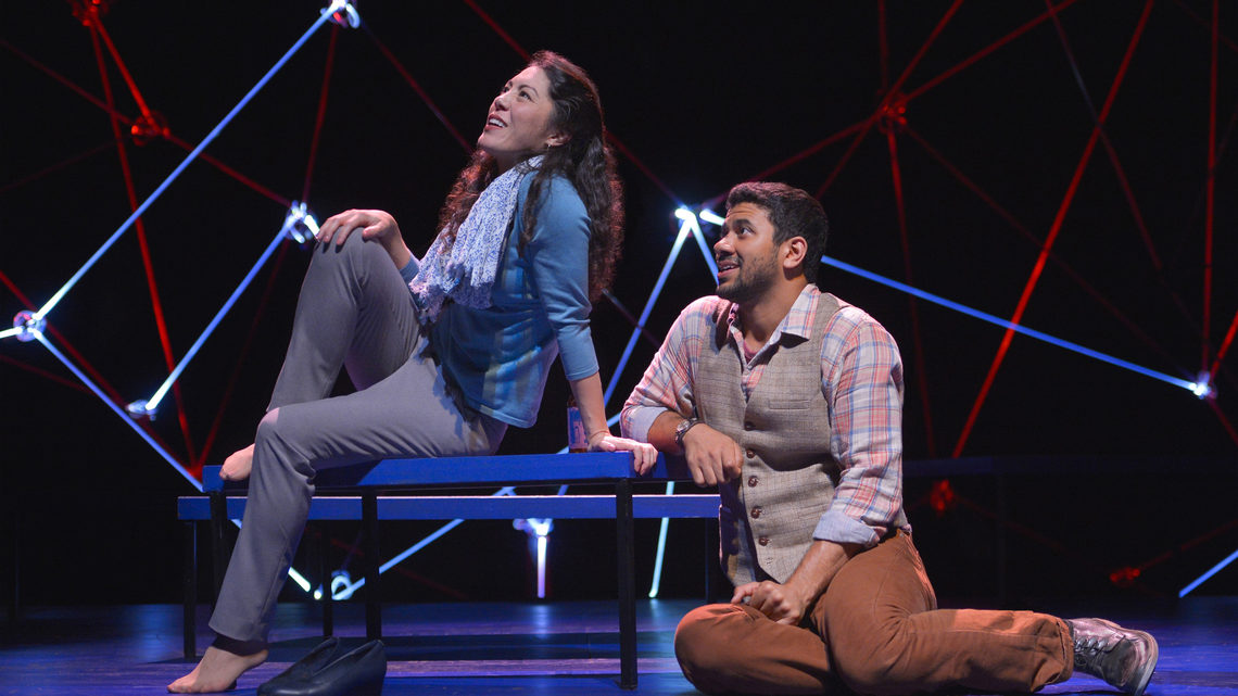 A scene from Constellations: a man and woman are on stage, she is sitting on a bench he is sitting on stage looking at her