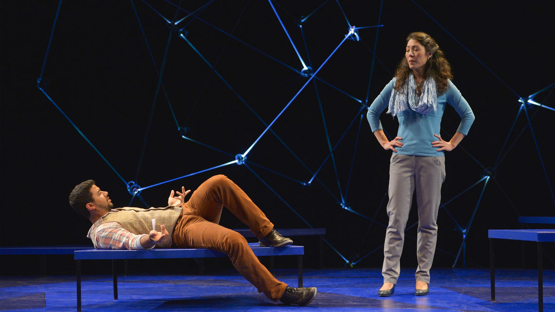 A scene from Constellations: a man and woman on stage he is laying down on a bench, she is standing with hands on her hips