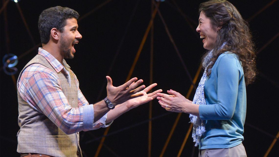 A scene from Constellations: a man and woman on stage he explaining something to her, she is laughing