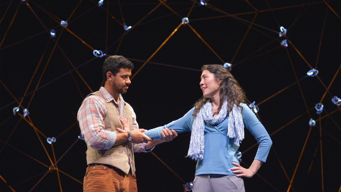 A scene from Constellations: a man and woman on stage. He is holding her arm against his chest