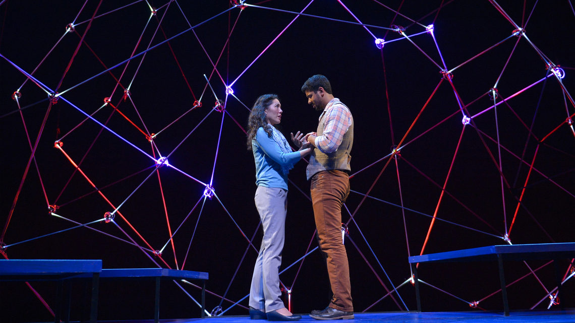 A scene from Constellations: a man and woman on stage holding hands
