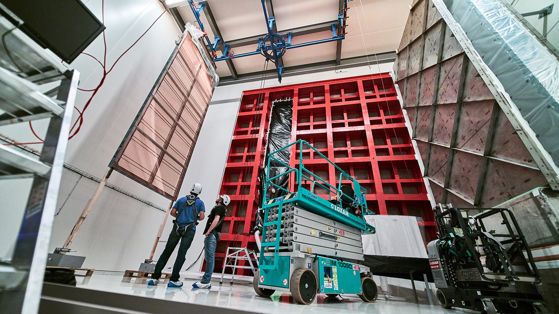Technicians look up at an APA hanging near the red ProtoDUNE frame